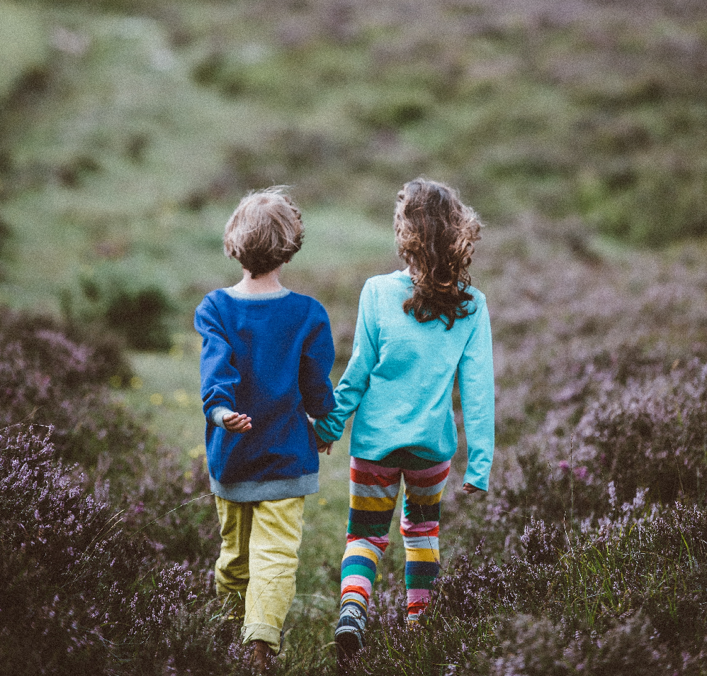 Two children walking through a field