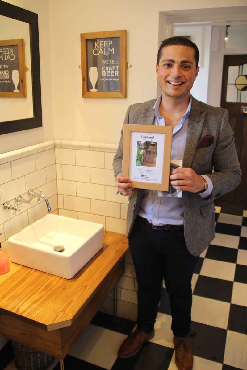 The Beaumont Arms' landlord holding the pub's certificate for the 'Toilet Twinning'