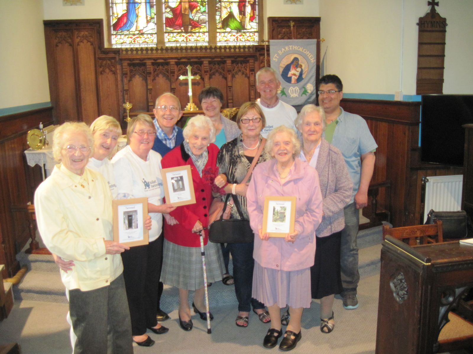 Members of Grange Moor holding the church's certificates for the Toilet Twinning