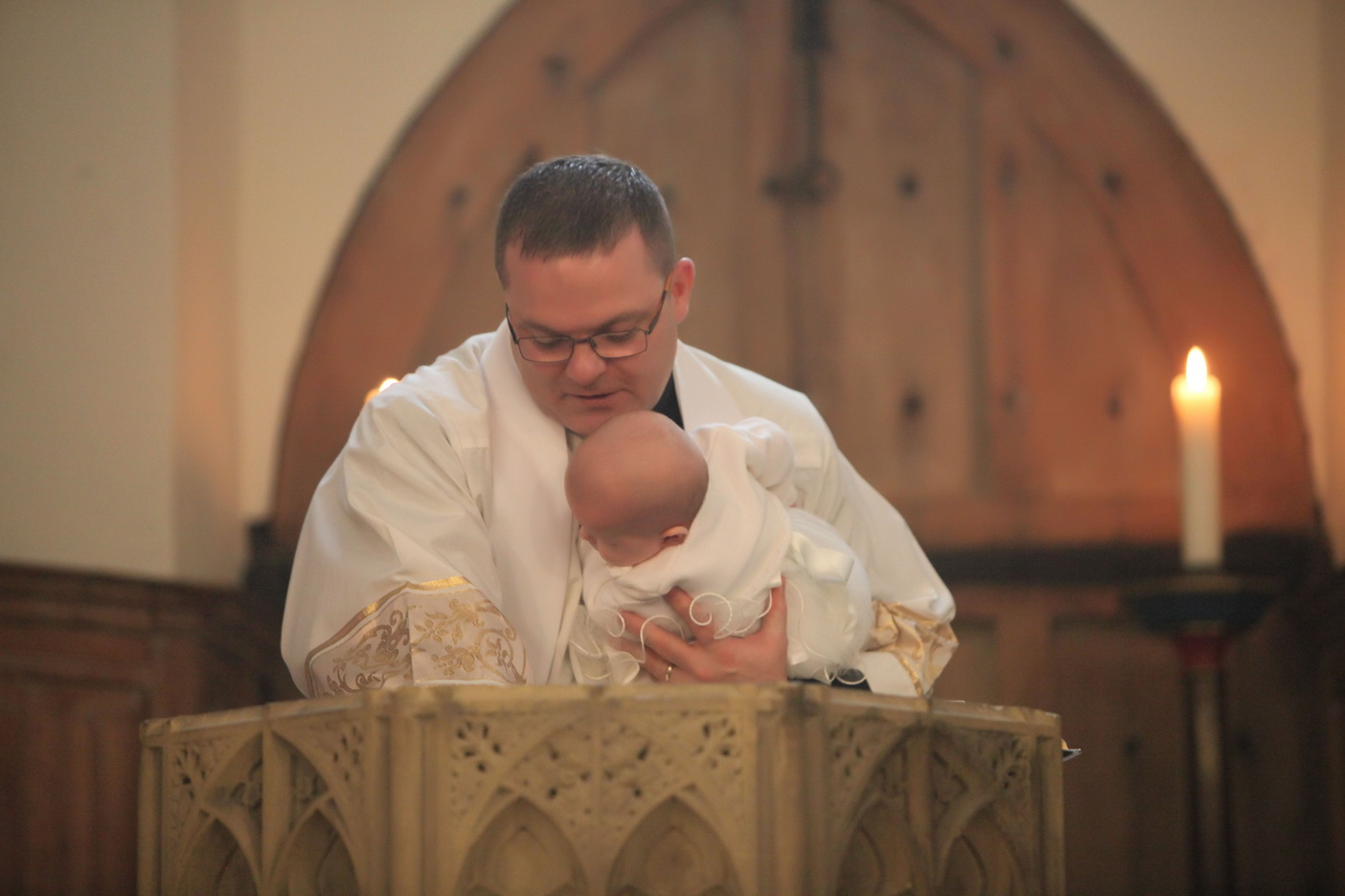 Fr Darren baptising a baby in his church