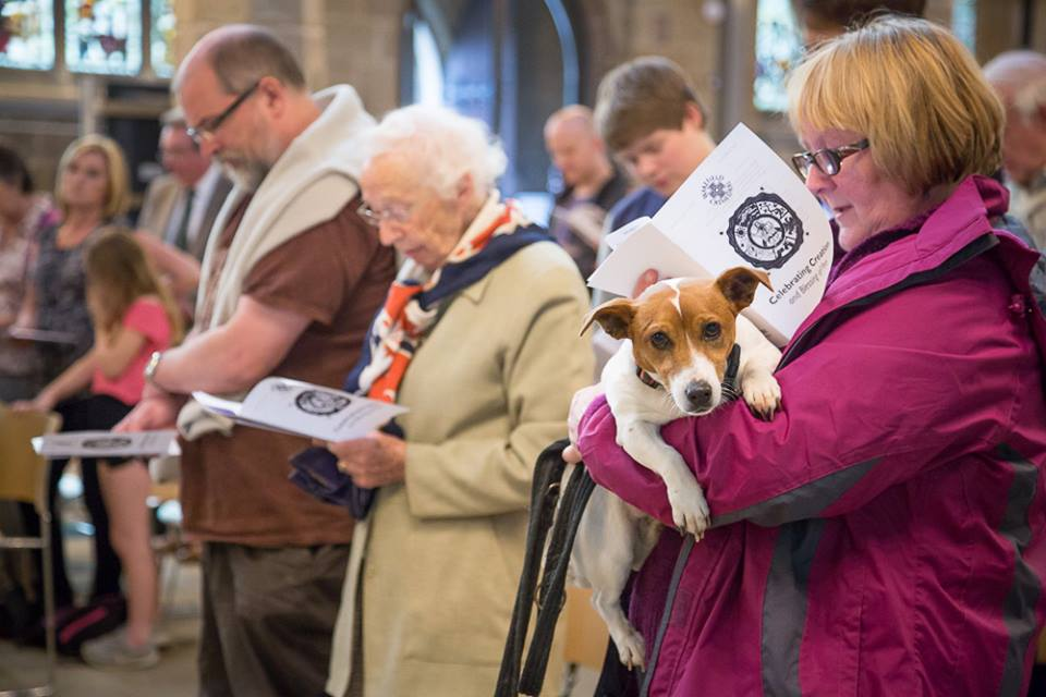 A member of the congregation holding her dog during the service