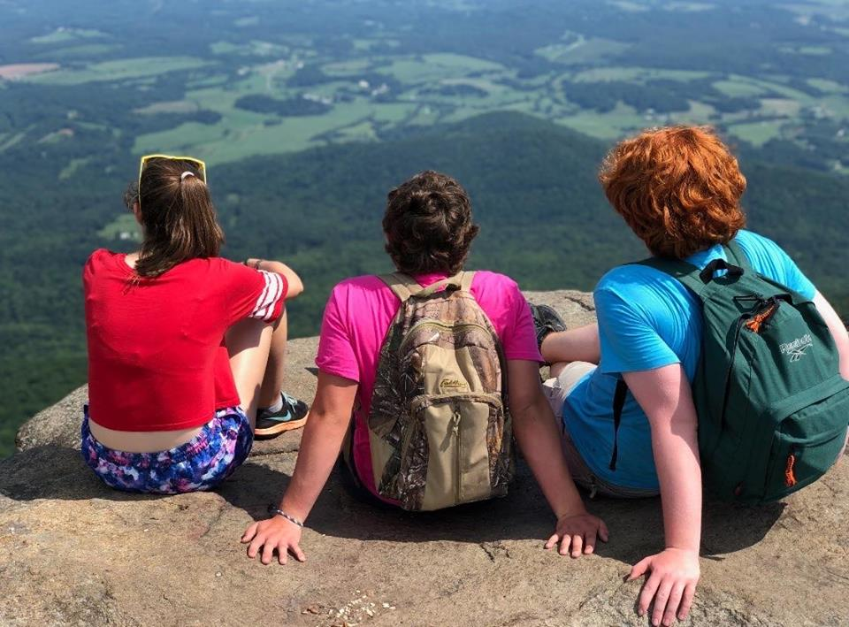 Three young people on a rock enjoying the view into the distance