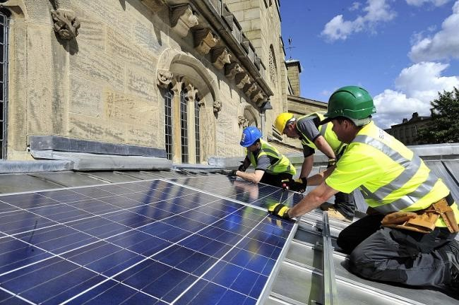 Solar panels being fitted on to a church