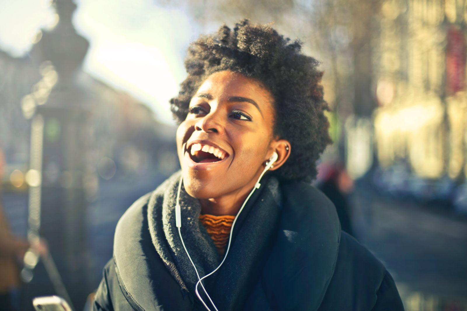 A young person singing along to music with their earphones in