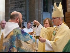 The Bishop of Leeds pours balsam (perfume) into the oil of Chrism (anointing)