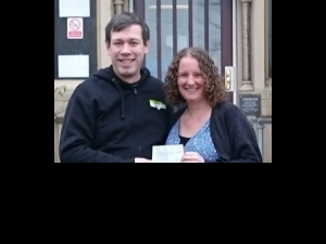 Paul Blakey of Street Angels hands lost property money over the St Augustine's charity