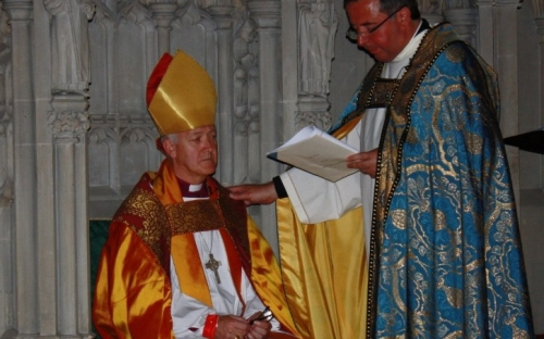 Dean, Jonathan Greener places Bishop NIck in the Episcopal Chair or Cathedra